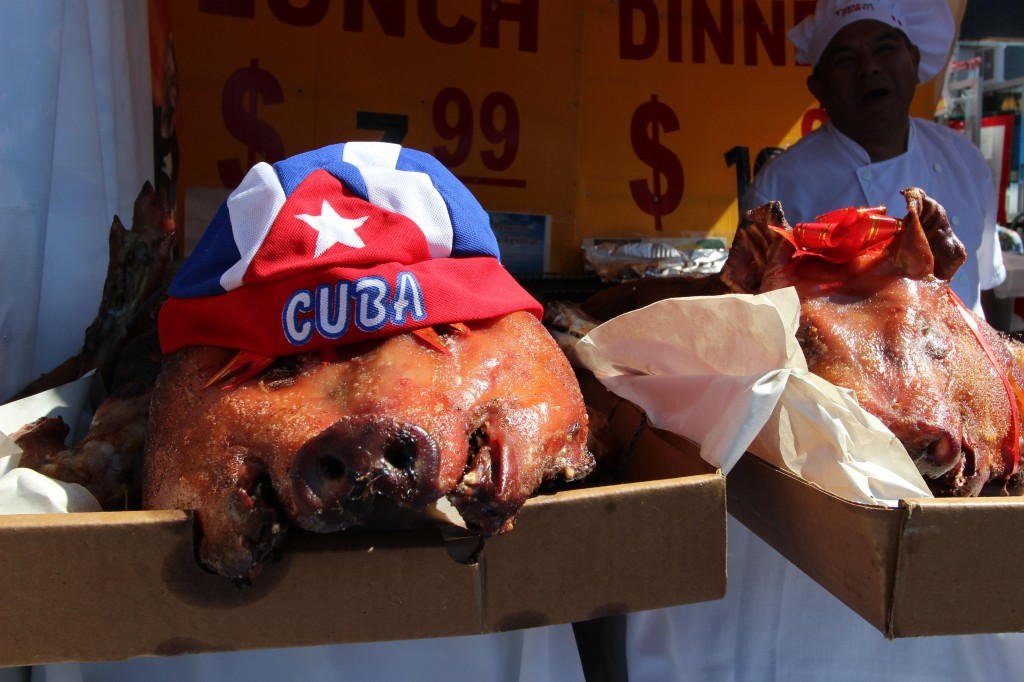 A whole roasted pig with a hat of the Cuban flag on its head