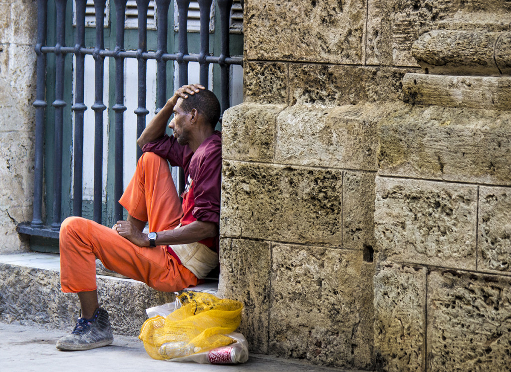 A homeless man, sitting on one of the sidewalks in Old Havana.