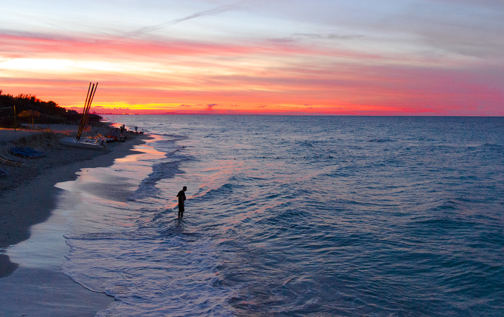 A local fisherman fishing near the shore of the beach, and the view of the sunset over the horizon.