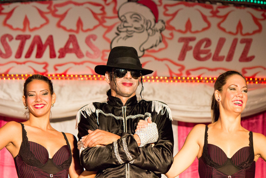 A Michael Jackson impersonator standing on stage with one girl on each side.