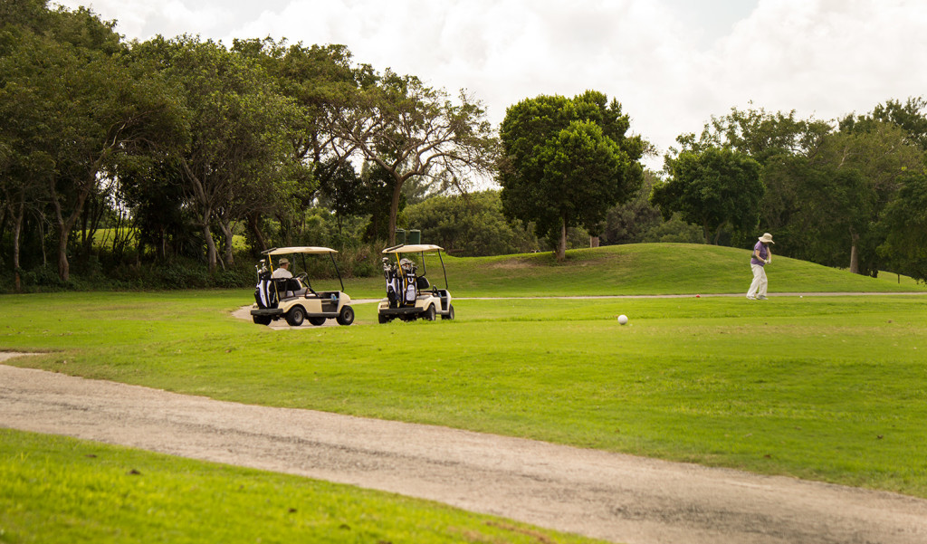 Two golf carts and one person playing golf in a golf course.