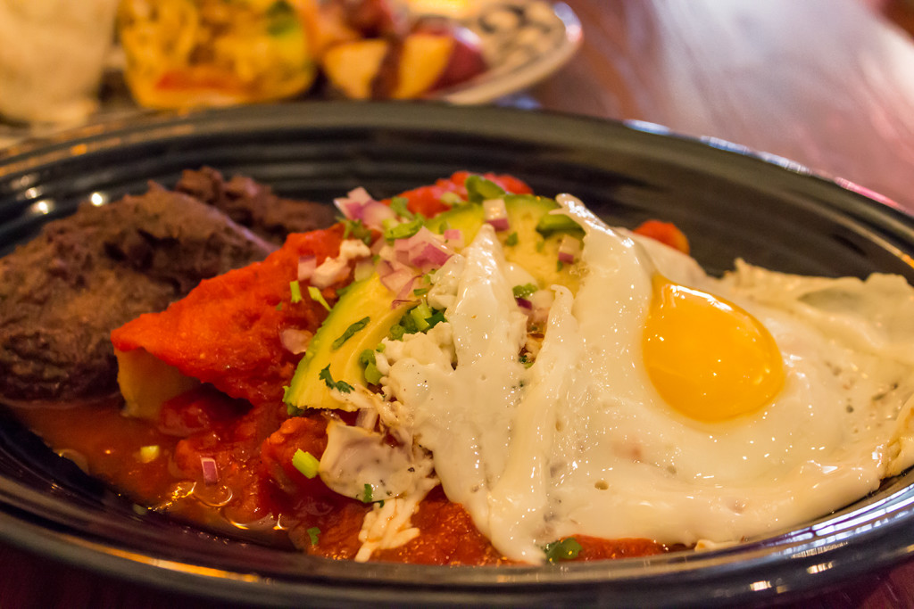 A mexican dish called enchiladas pachucas. Enchiladas Pachuca — slow roasted lamb, tomato & chipotle salsa, sour cream, panela (unrefined whole cane sugar), cilantro, served with a friend egg on the side.
