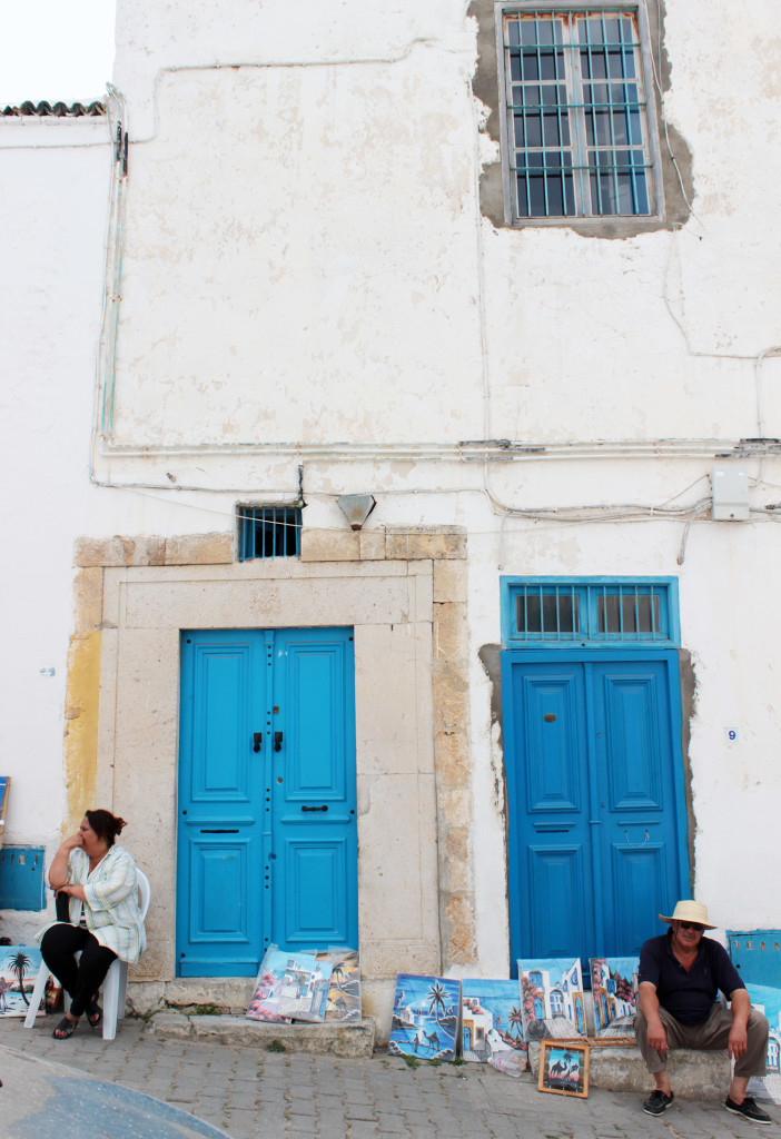 A man and a woman sitting outside houses with two blue doors in the city of Sidi Bou Said, Tunisia.