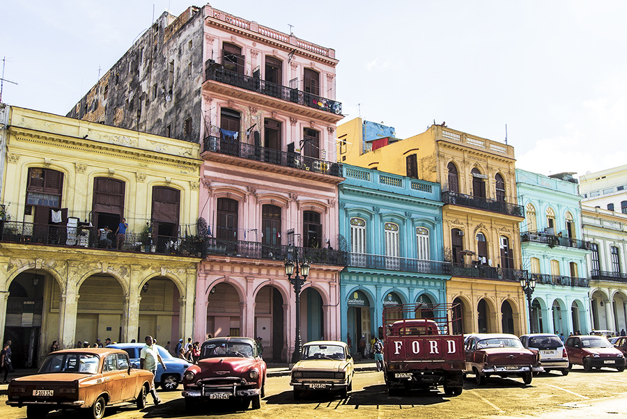 A street in Havana, Cuba with colourful buildings in the background and outside of the buildings many old timer cards.