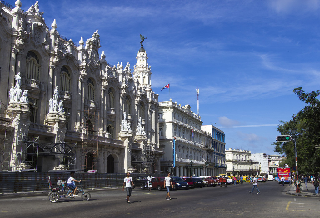 Photo of the Gran Teatro de La Habana and people crossing the street in front of it on a sunny day