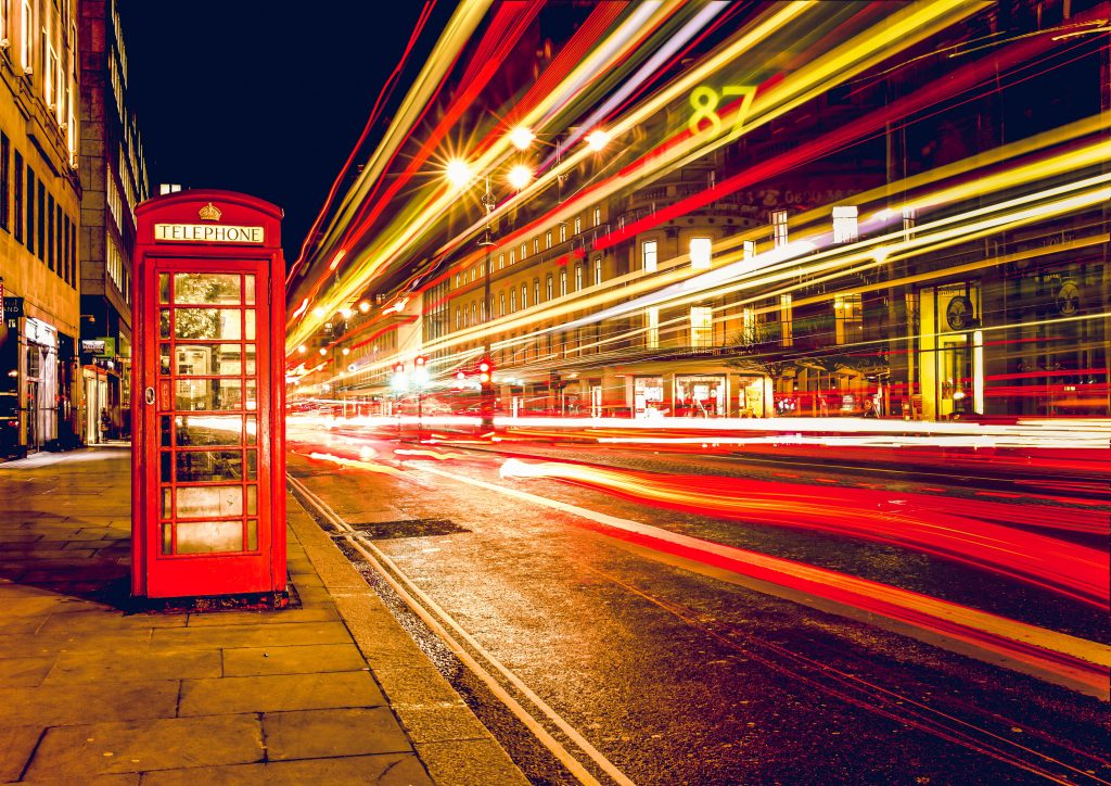 A night photo of a street in London, England. There is a red telephone booth and the trails of a fast moving car on the street.