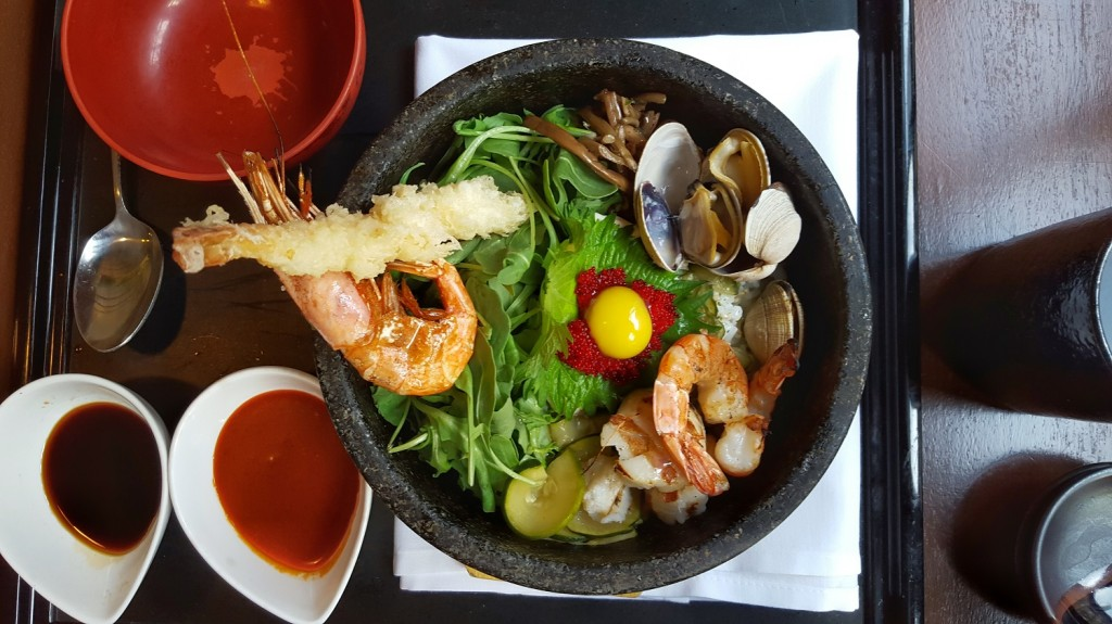 Seafood bowl containing shrimp tempura, tobiko, scallops, seasoned vegetables, quail egg, rice, in hot stone bowl.