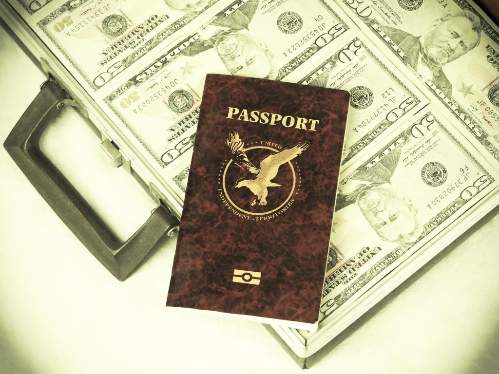 Photo of a passport on top of a suitcase full of fifty dollar bills.