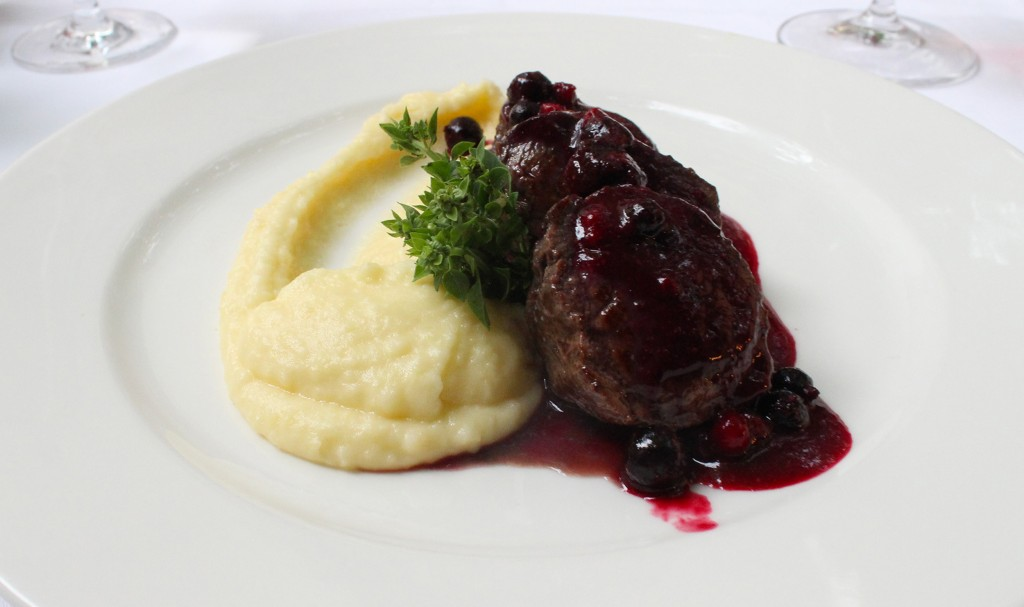venison fillet with blueberries served alongside a silky potato pure.